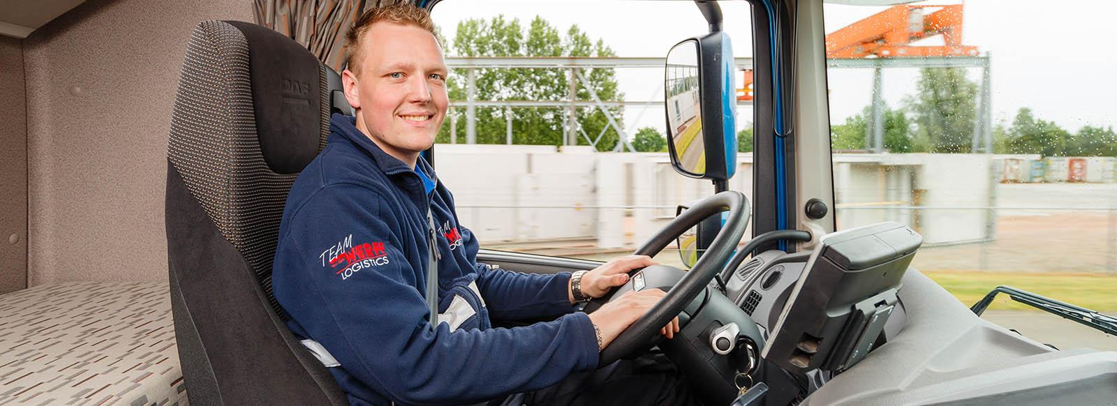 Chauffeur blij kijkend achter stuur in cabine vrachtwagen