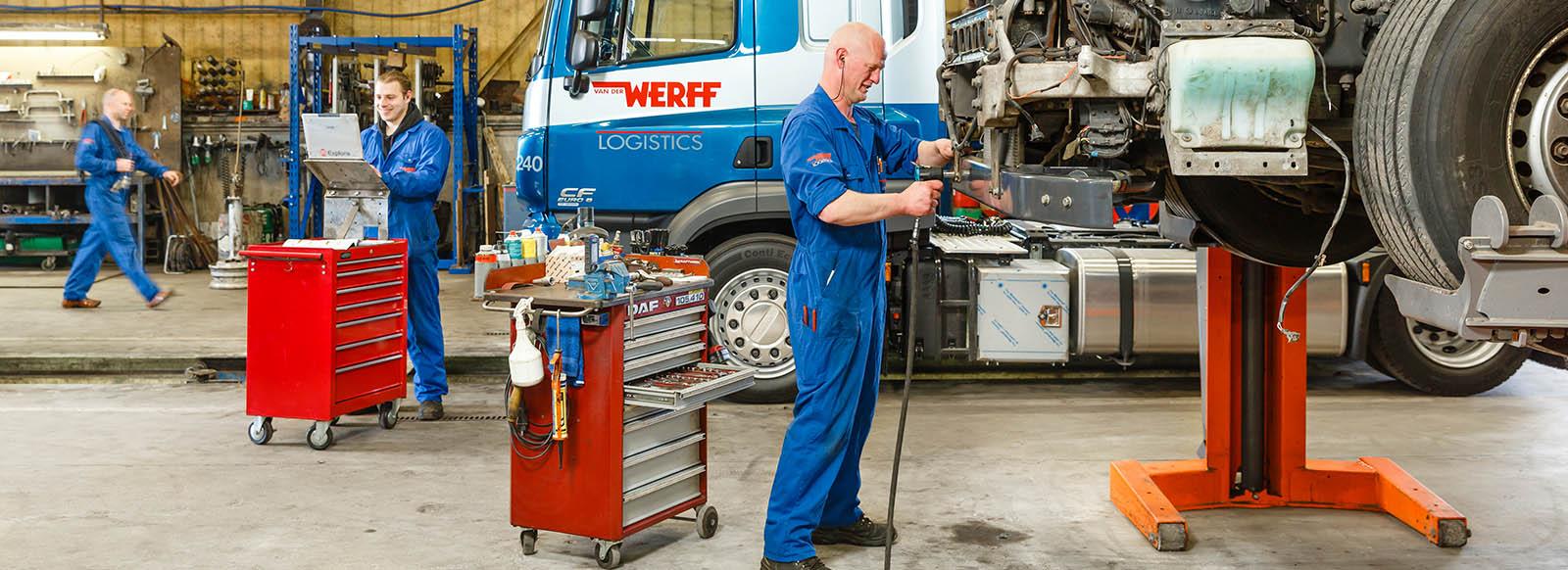 Monteurs werkend in werkplaats aan vrachtwagens